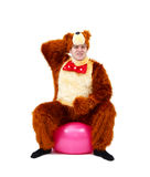 Funny man in bear costume on fitness ball isolated. In studio Stock Images