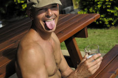 Funny man with beret. Man with french beret, sticking out one's tongue and drinking water Royalty Free Stock Photo