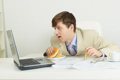 Funny man with big sandwich at office Royalty Free Stock Photos