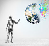 Funny man in body suit looking at colorful splatter earth Stock Image