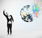 Funny man in body suit looking at colorful splatter earth Royalty Free Stock Image