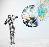 Funny man in body suit looking at colorful splatter earth Stock Photo