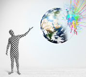 Funny man in body suit looking at colorful splatter earth Stock Photography