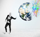 Funny man in body suit looking at colorful splatter earth Royalty Free Stock Images