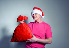 Funny man in cap Santa Claus with red bag of gifts Royalty Free Stock Image