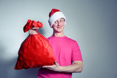 Funny man in cap Santa Claus with red bag of gifts Royalty Free Stock Images