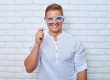 Funny man in casual clothes holding paper glasses while posing a Royalty Free Stock Photos