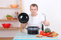 Funny man cooking in the kitchen Royalty Free Stock Images