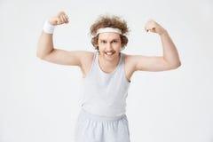Funny man demonstrates biceps, showing teeth looking at camera Stock Photo