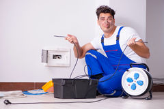 The funny man doing electrical repairs at home. Funny Man doing electrical repairs at home Royalty Free Stock Image