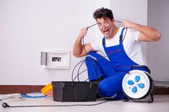 The funny man doing electrical repairs at home Stock Photo