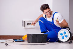 The funny man doing electrical repairs at home. Funny Man doing electrical repairs at home Stock Photo