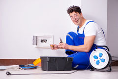 The funny man doing electrical repairs at home. Funny Man doing electrical repairs at home Royalty Free Stock Images