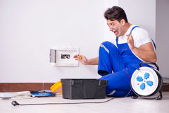 The funny man doing electrical repairs at home. Funny Man doing electrical repairs at home Royalty Free Stock Photos
