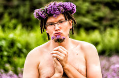 Funny man with dreadlocks holds a flower Stock Photo