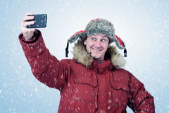 Funny man dressed in winter clothes make selfie on smart phone Stock Photography