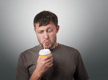 Funny man drinking from a disposable paper cup with a straw Stock Image
