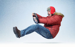 Funny man driver car in winter clothes with steering wheel. Flight through the snow concept Royalty Free Stock Photo