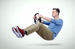Funny man drives a car with a steering wheel. On background Stock Photography