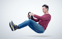 Funny man drives a car with a steering wheel Stock Images