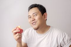 Funny Man Eating Red Apple. Portrait of funny Asian man eating fresh red apple, healthy fruit, healthy lifestyle indonesian malaysian thai diet food male person stock photography