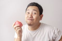 Funny Man Eating Red Apple. Portrait of funny Asian man eating fresh red apple, healthy fruit, healthy lifestyle indonesian malaysian thai diet food male person royalty free stock photography
