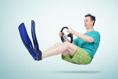 Funny man in flippers and shorts with a steering wheel. Concept of going on vacation royalty free stock photos