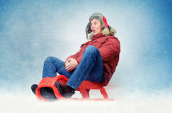 Funny man fly on a sled in the snow, concept winter fun Royalty Free Stock Photography
