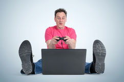Funny man gamer sitting on the floor playing on laptop Royalty Free Stock Photo