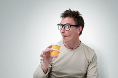 Funny man in glasses drink through a straw Stock Photo