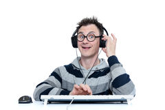 Funny man in glasses and headphones with keyboard in front of computer. Royalty Free Stock Image