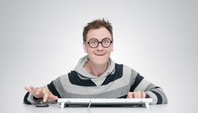 Funny man in glasses with a keyboard in front of computer Stock Image