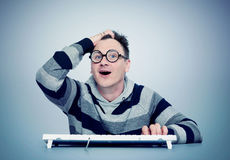 Funny man in glasses with keyboard in front of computer. Eureka! Stock Image