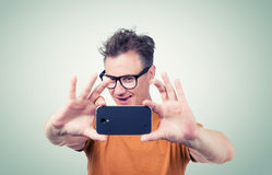 Funny man in glasses photographed by smartphone Stock Photos