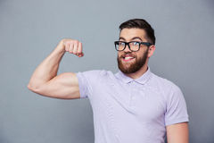 Funny man in glasses showing his muscles Royalty Free Stock Photos