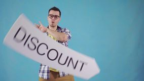 Funny man with in glasses with a sign discount. On blue background stock footage