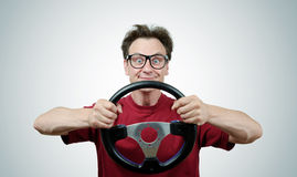 Funny man in glasses with a steering wheel, car drive concept Stock Images