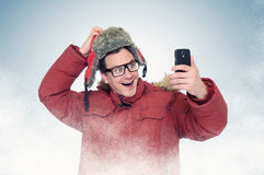 Funny man with glasses and winter clothes make selfie smart phone Royalty Free Stock Photo