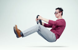 Funny man in goggles drives a car with a steering wheel Royalty Free Stock Photography