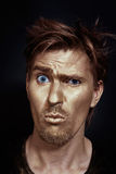 Funny man with golden make-up. On a black background Stock Image