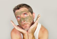 Funny man with green seaweed facial mask on his face posing in front of the mirror mocking on himself using skin care beauty prod stock photo