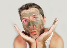 Funny man with green seaweed facial mask on his face posing in front of the mirror mocking on himself using skin care beauty prod. Young funny man with green Royalty Free Stock Photo