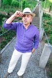 Funny man in hat is fooling around near stone stairs outdoors. Funny man in hat is fooling around and humorously bows near stone stairs outdoors royalty free stock photos