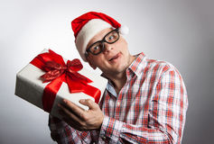 Funny man in a hat Santa with a Christmas present in his hand. Royalty Free Stock Image