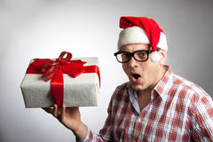 Funny man in a hat Santa with a Christmas present in his hand. Royalty Free Stock Images