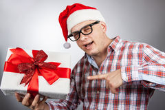 Funny man in a hat Santa with a Christmas present in his hand. Royalty Free Stock Photography