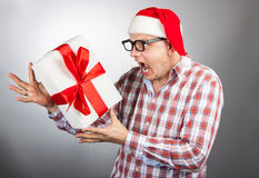 Funny man in a hat Santa with a Christmas present in his hand Stock Image