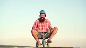 Funny man having fun on children bicycle. Funny crazy man. Fathers day. A funny bearded man is riding a kids bicycle . Funny man having fun on children bicycle stock footage