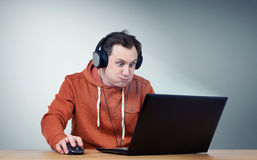 Funny man in headphones with laptop. Gameplay Stock Photos
