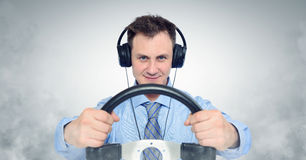 Funny man in headphones with a steering wheel. Car drive concept stock image